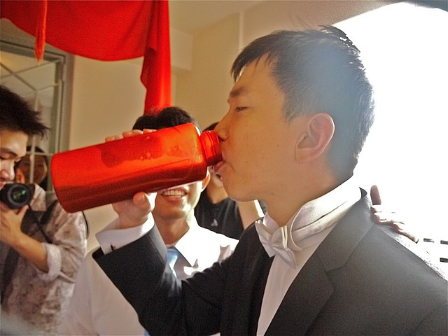 640px-Groom_drinking_from_bottle_during_Chinese_wedding_door_game