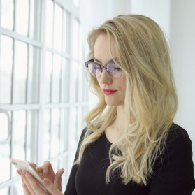 Portrait of a young blonde woman in glasses with a phone at the big window